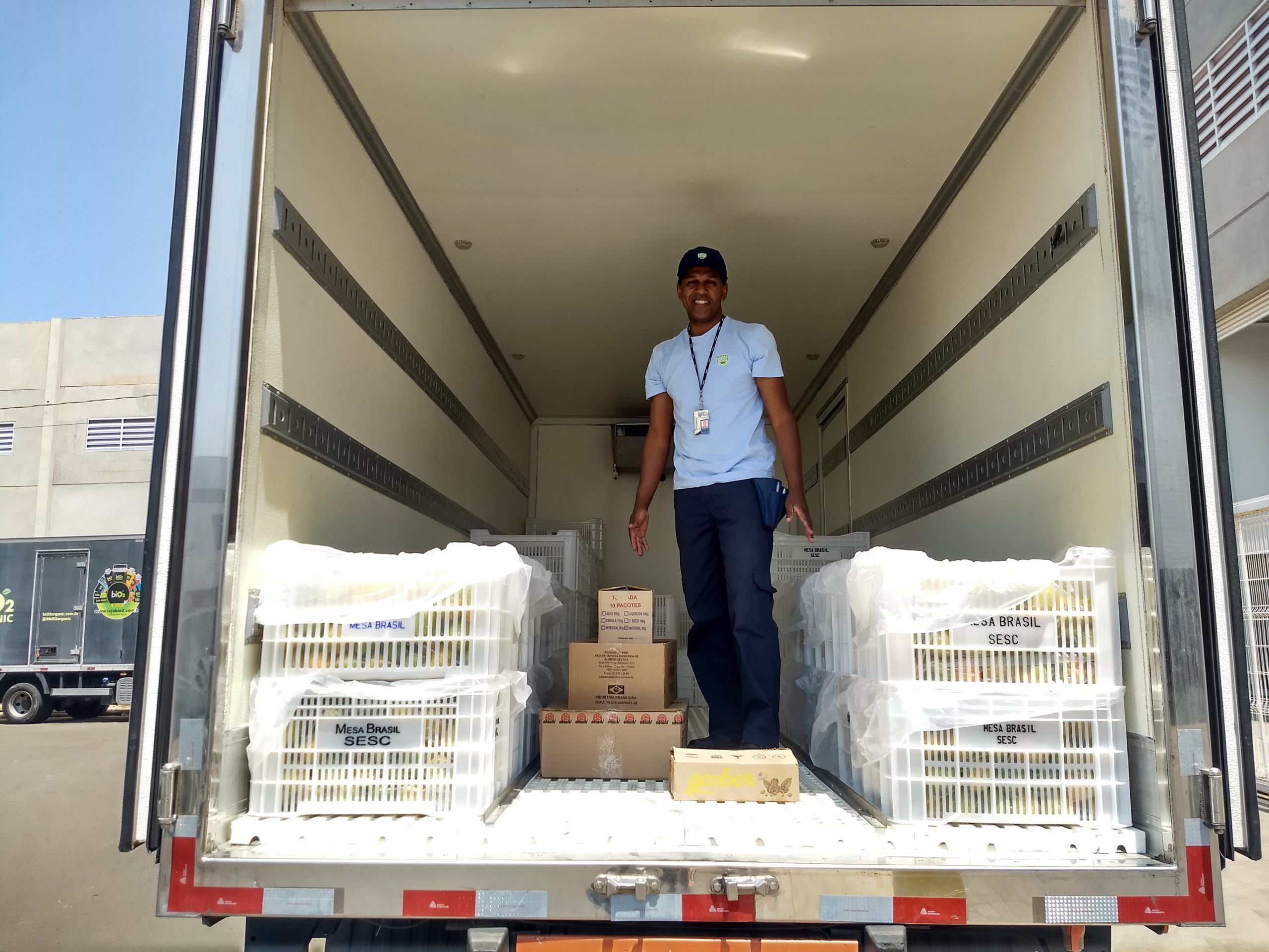 Funcionário do Mesa Brasil recebendo doações da Lourenço, ele está dentro do Baú do Caminhão do Mesa Brasil, sorrindo, com as caixas de doação da Lourenço Alimentos no chão.